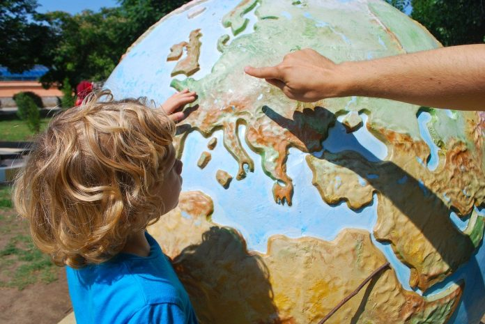 child pointing at a globe
