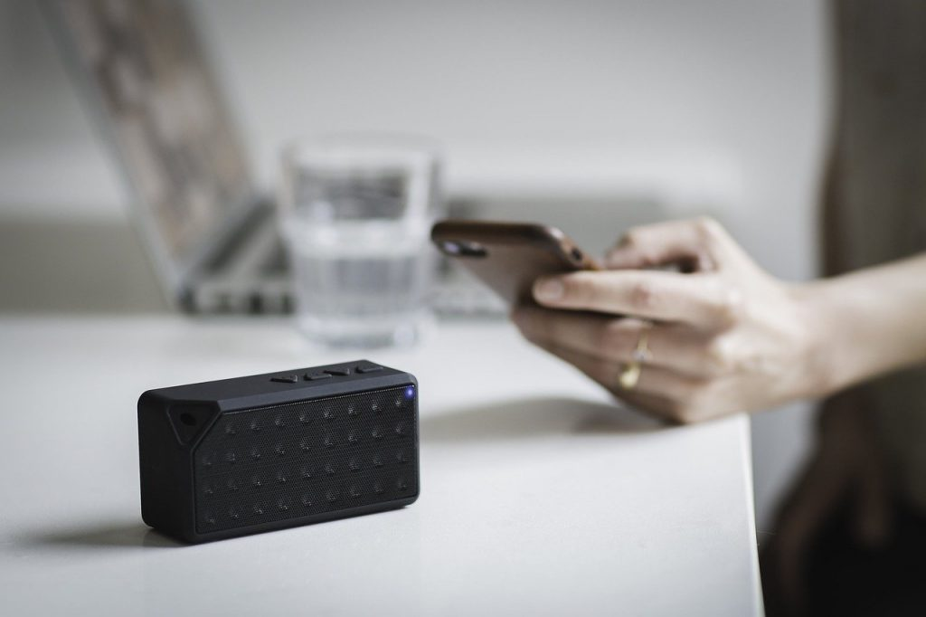 person turning on a bluetooth speaker