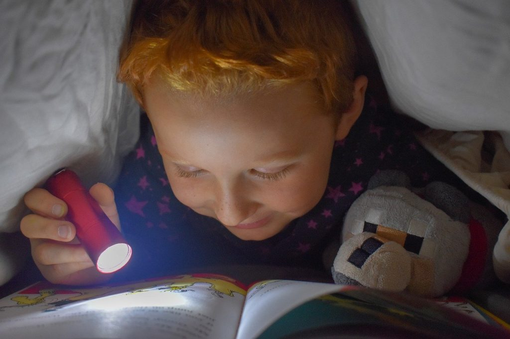 little boy reading a book under a blanket with flashlight