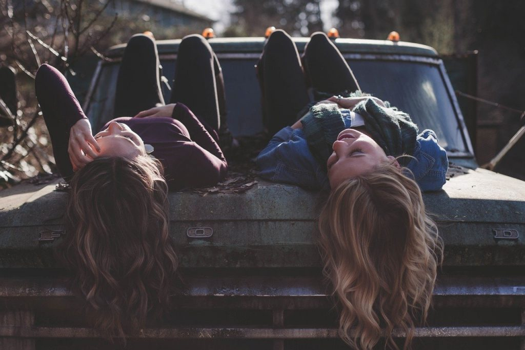girls laying on a truck